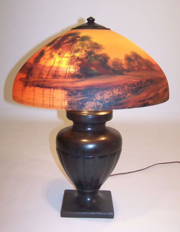 Handel lamp with original reverse painted shade. Has original cloth label on the bottom of the base and is signed on the shade and also signed in the heat ring. American, early 20th century.