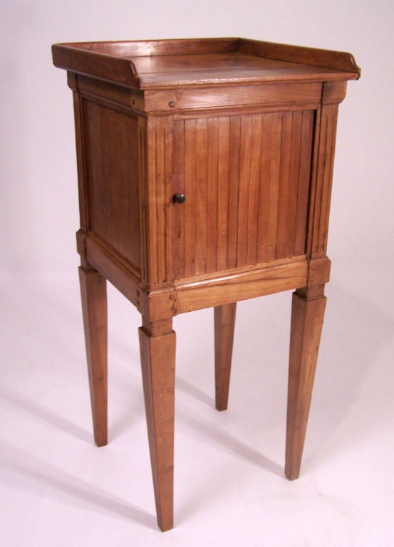 Cherrywood side cabinet with tambour sliding drawer, having a wood gallery and standing on tapering square legs, French, late 18th century.