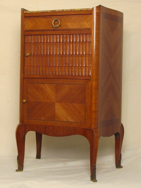 A beautifully handcrafted small side cabinet table of tulip wood and mahogany with a tambour sliding middle door, lower cabinet and top single drawer and having its original marble top, France, early 20th century.