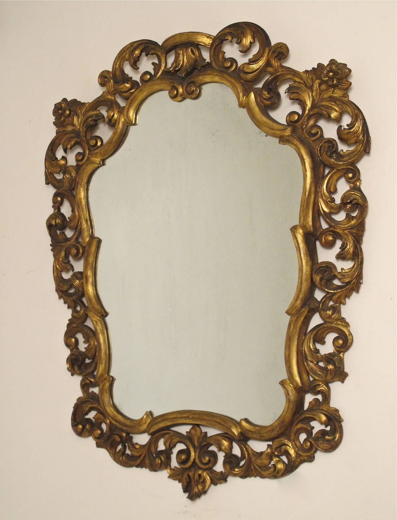 Shapely carved giltwood framed mirror by Fratelli Paoletti with C scroll and floral design. Italian, circa 1950.