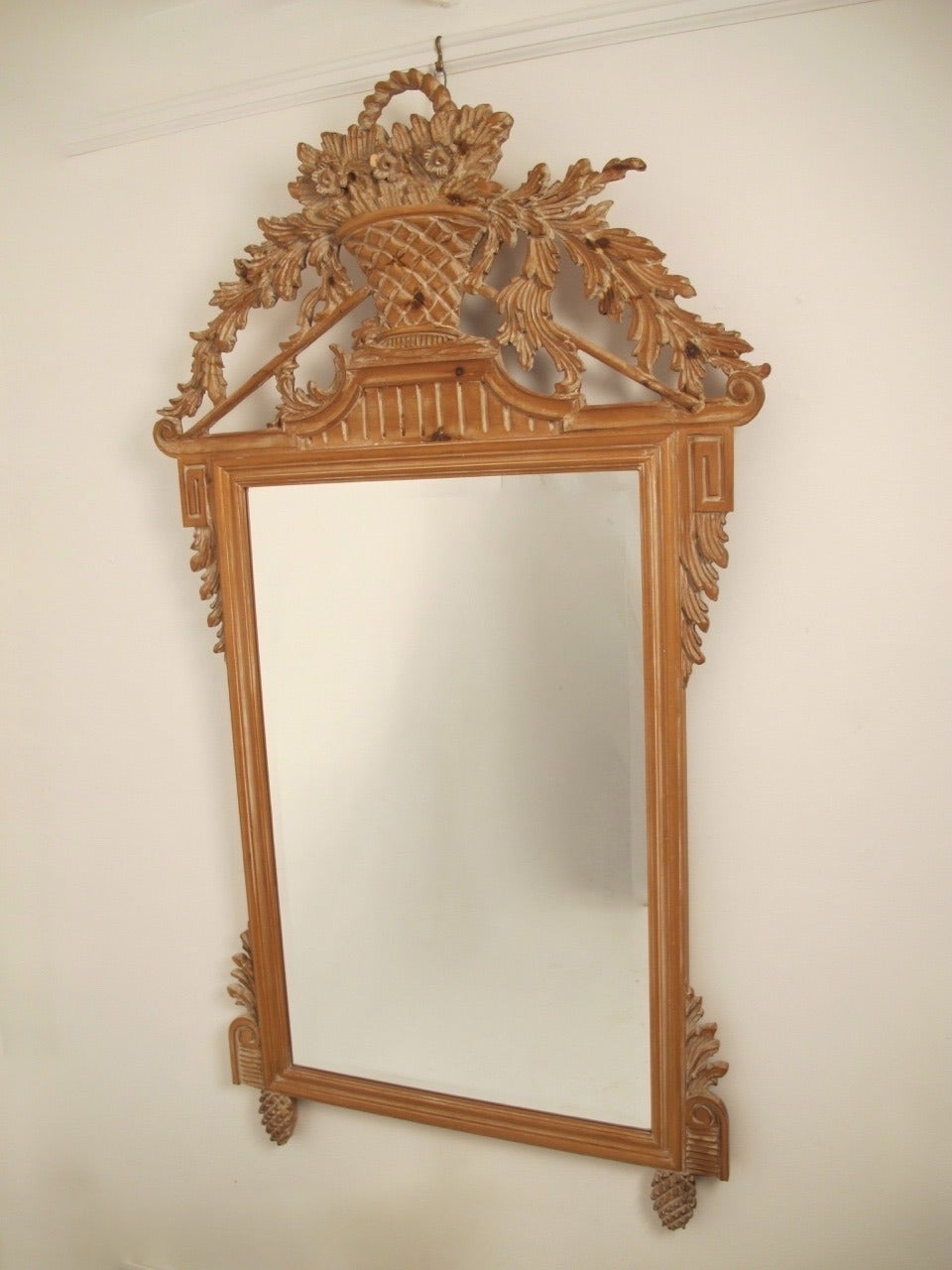 An elaborately hand-carved pine frame with beveled glass mirror and white washed finish. Centre topped by a basket of flowers, scrolling acanthus leaves draping down both sides and flanked by Greek key blocks, ending on pineapple feet. Symbols of
