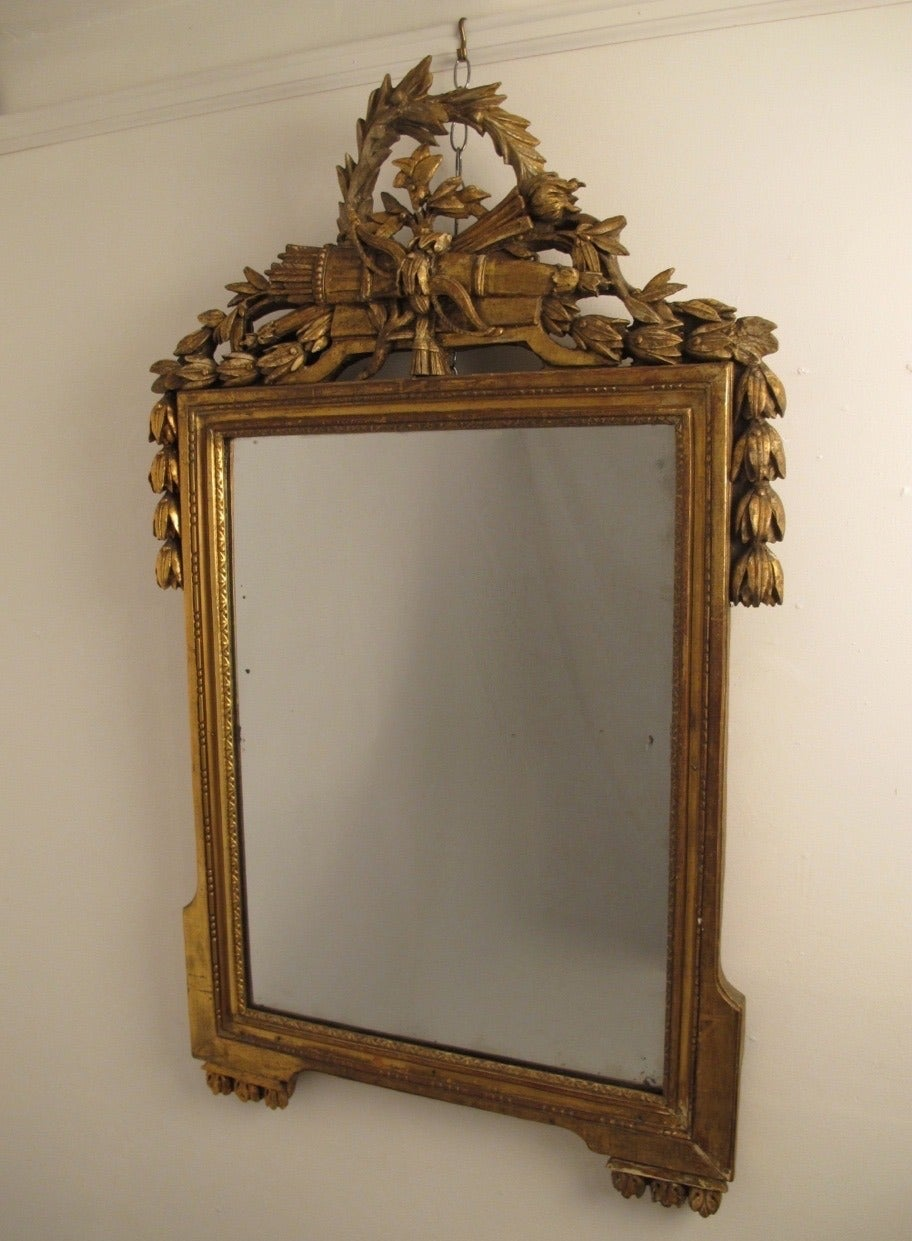 A highly carved and gilt wood frame with laurel leaves, quiver and bell flowers. Has original glass plate mirror, the original gilding is worn and aged in areas, France, circa 1760.
