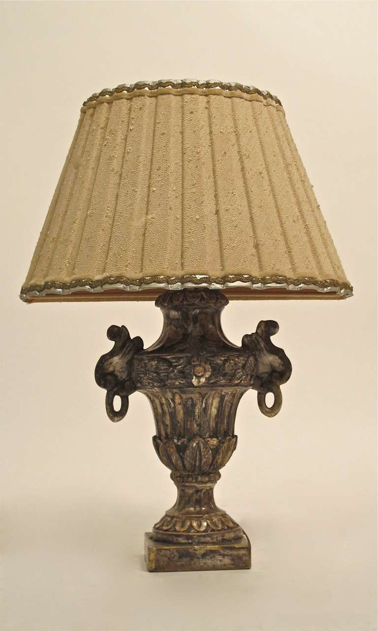 An 18th century carved and gessoed wood with silver gilding half urn, converted to a lamp. Vintage custom made raw silk half shade has some small tears on the inside lining. Dimensions below include the shade.