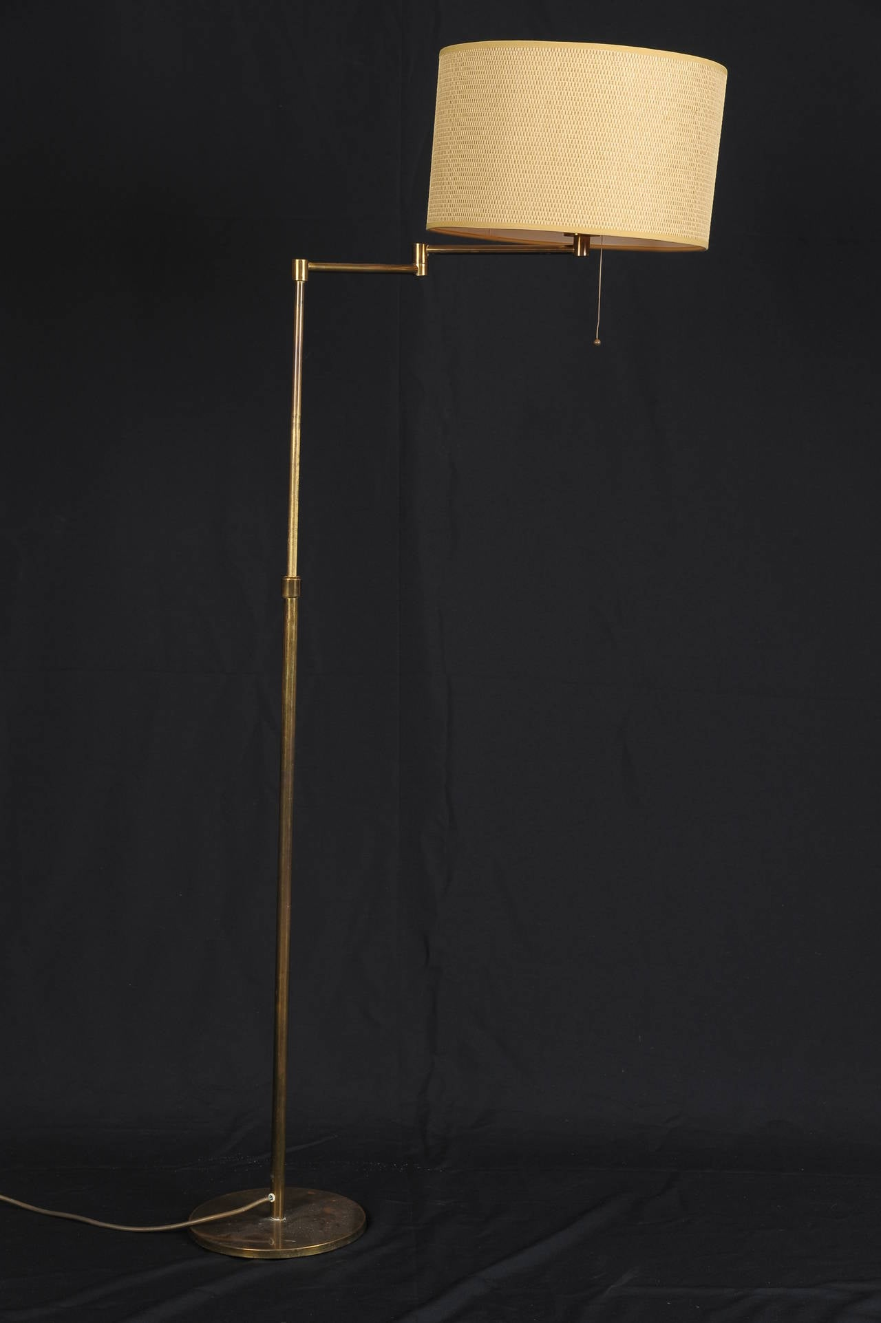 Adjustable height and swing arm antique brass floor lamp in Style of Arredoluce. Lamp is in original condition. Full extended arm is 25 inches.
