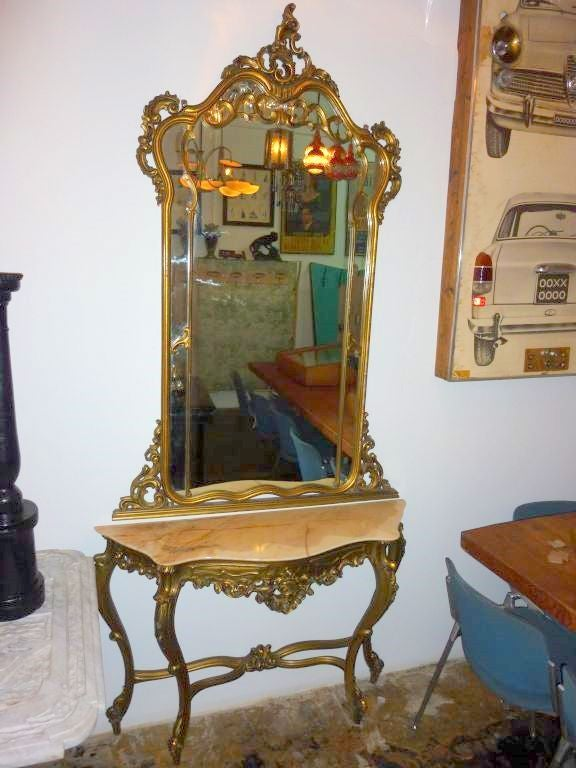 Three-piece entry table with marble top and mirror.