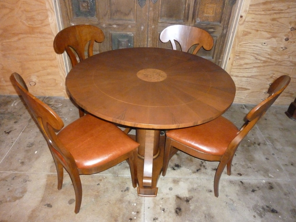Italian table, central leg, four chairs reupholstered in leather. Table top intarziato (inlaid woodwork) easy sets six persons. Table dimensions: Measures: Height 31.5. Diameter 43.5.