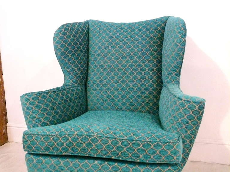Pair of Mid-Century wingback chairs with incredible lines. Curves abound with scrolled arms, dipped back and flared wings. Pull them up to your favorite cozy spot. Newly refinished in dark chocolate and upholstered in a turquoise Moroccan inspired