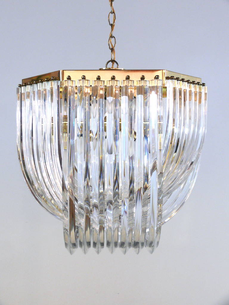 Extravagant oversized Italian Lucite swag chandelier with triple draping and a hexagonal brass frame. Its 11 sockets hold 40w candelabra bulbs.