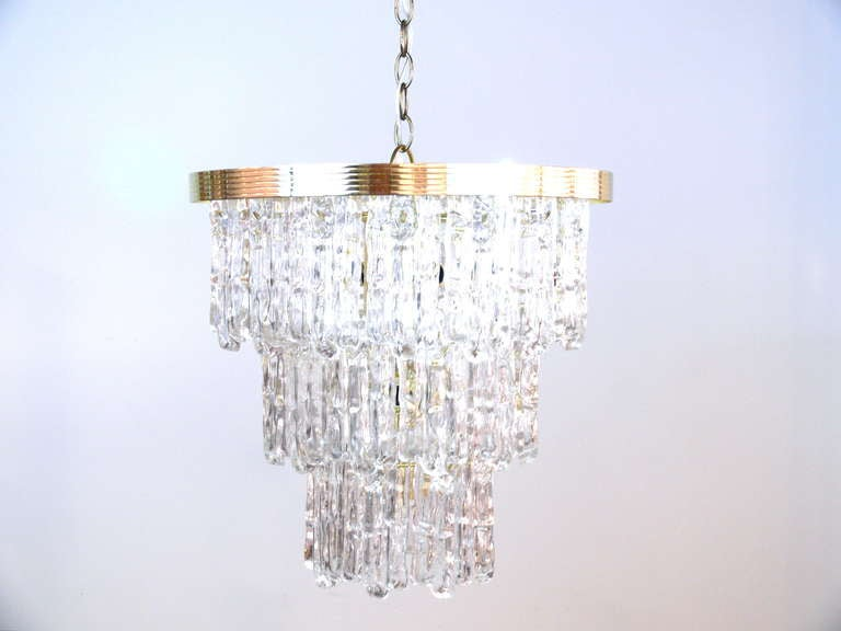 Beautiful three-tiered Lucite chandelier suspended from a brass frame reminiscent of Venini crystal chandeliers.