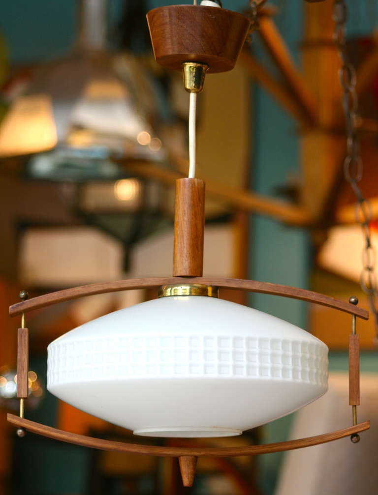 As seen in the recent episode of Mad Men, charming Danish teak pendant light with milk glass shade.