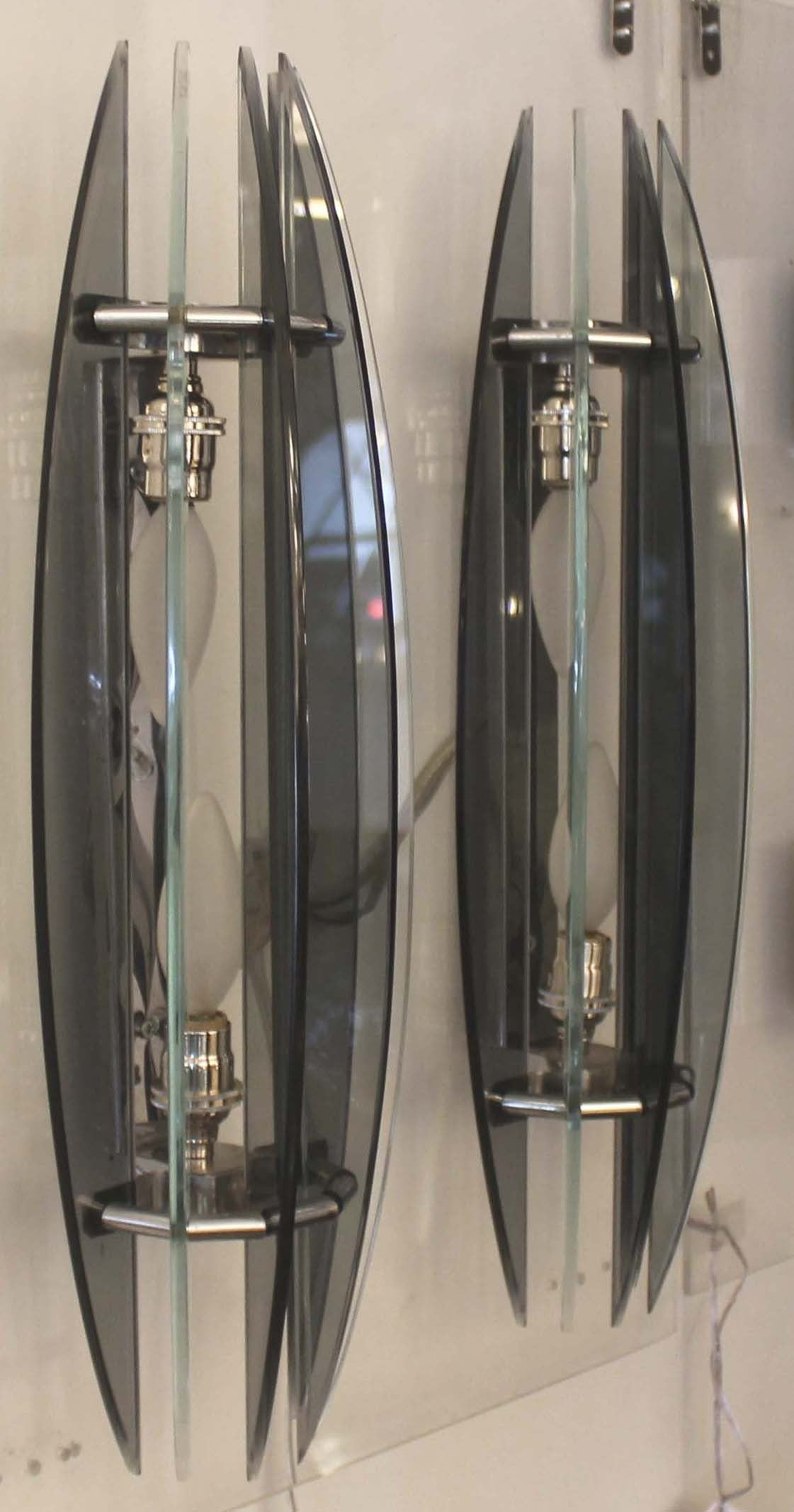Incorporating six alternating gray and clear glass slabs that are attached to a small chromed metal frame. Each sconce has two candelabra sockets that can go up to 60 watts each. Veca was an Italian company active in the 1960s and 1970s specialized
