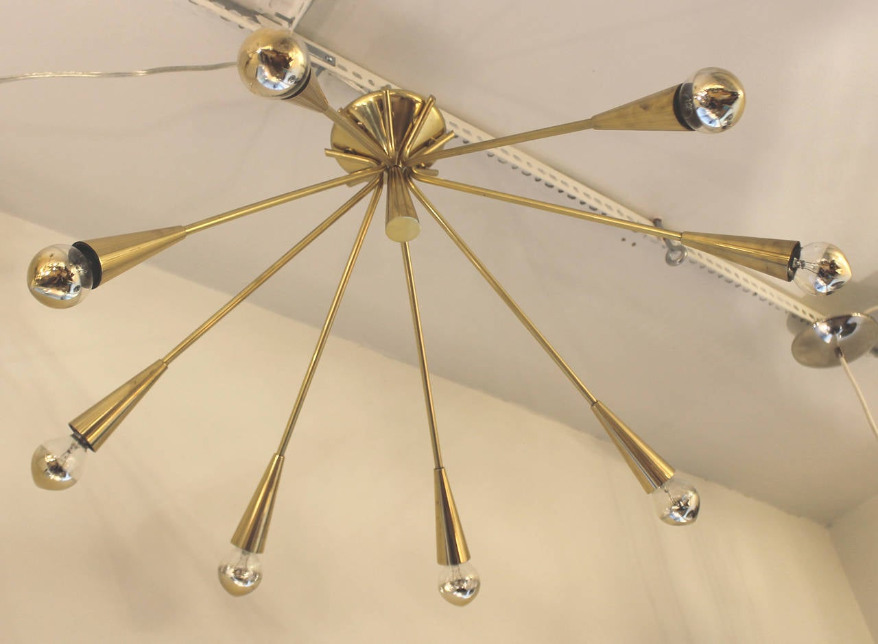 Elegant brass chandeliers with eight arms ending in a light bulb. Designed by Oscar Torlasco for Lumi. Documented. They can be flush mounted or hang on a chain. Price is per fixture.