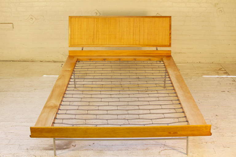 This full-sized bed, designed by George Nelson and manufactured by Herman Miller, features a solid European Birch frame, tubular steel legs and supports, and a woven-cane panel headboard. This piece was part of the historic