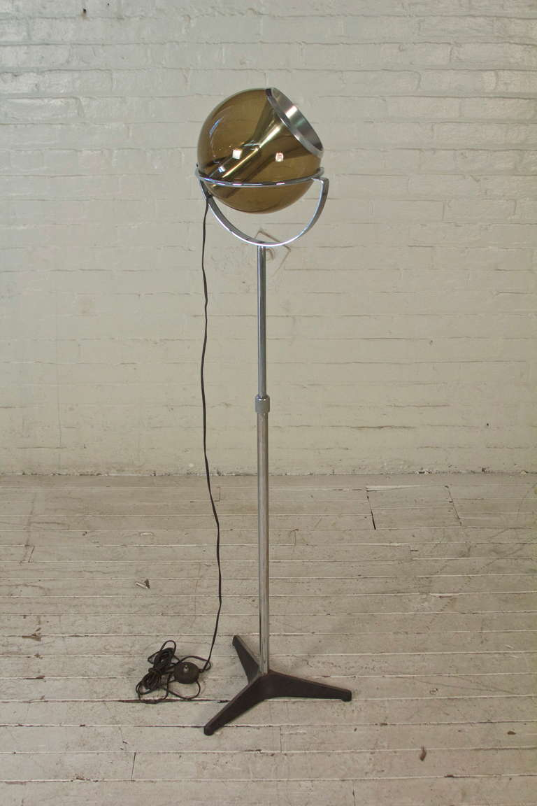 Directional floor lamp with extendable chromed-steel shaft, adjustable tinted-glass globe, and cast iron base. Designed by Frank Ligtelijn for RAAK of Amsterdam.