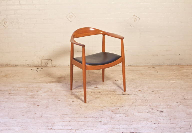 Vintage round chair by Hans Wegner for Johannes Hansen Cabinetmaker with Teak frame and original black leather seat. First designed in 1949, this is a great example of a classic chair-stamped Johannes Hansen.