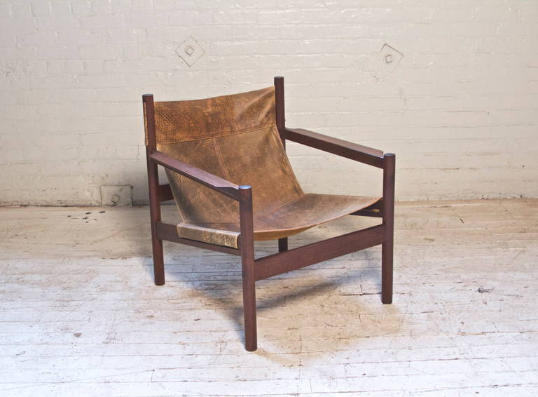This handsome, safari-style leather sling chair, features elegant lines, and a sturdy, fully-demountable construction. Demonstrating beautifully Arnoult's concept of