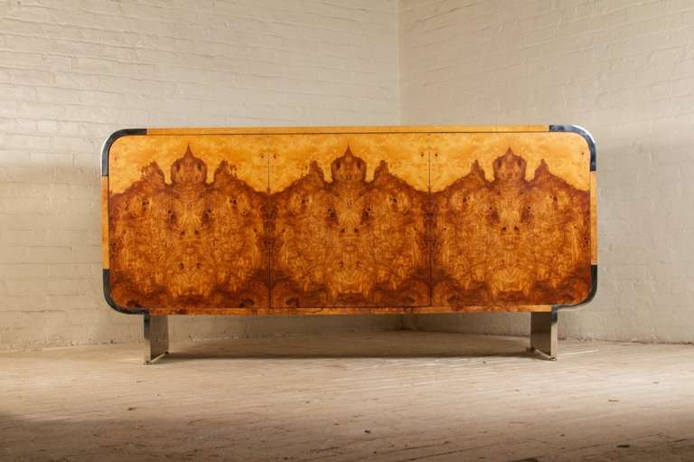 Great quality, unique sideboard by Pace Collection in an olive ash burlwood veneer. The veneer is book-matched and wraps around all sides of the cabinet. Structured with rounded polished stainless steel corners and legs. Three push open doors, which