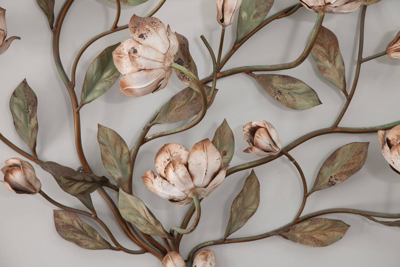 Pair of impressive vintage Italian painted tole sconces with branches sprouting deeply veined leaves and delicate flowers. Select blooms are fitted with candelabra light sockets.
