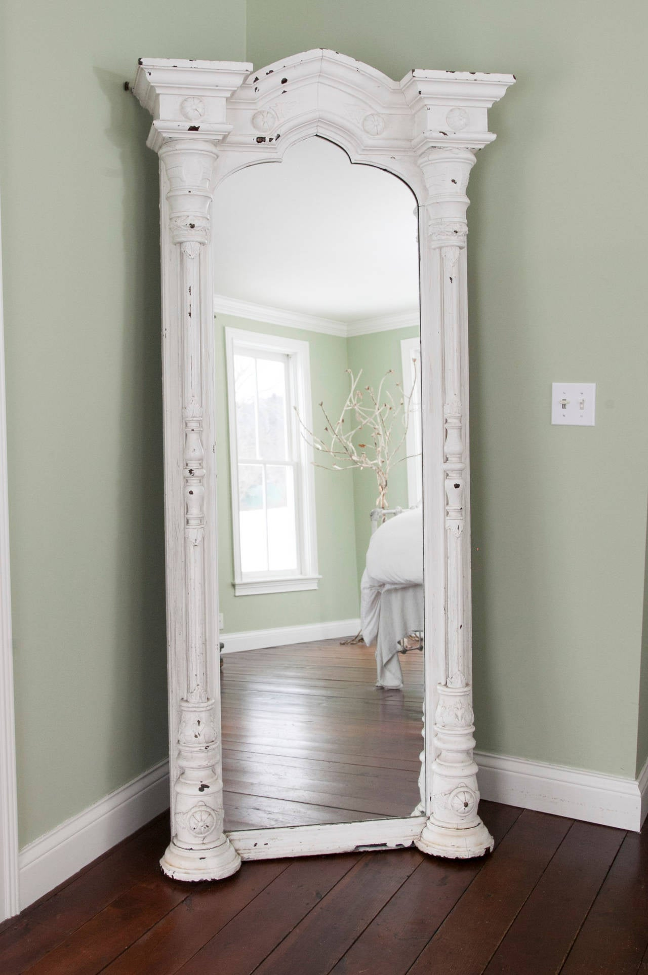 White painted walnut mirror, 19th century France, loaded with intricate architectural detail.