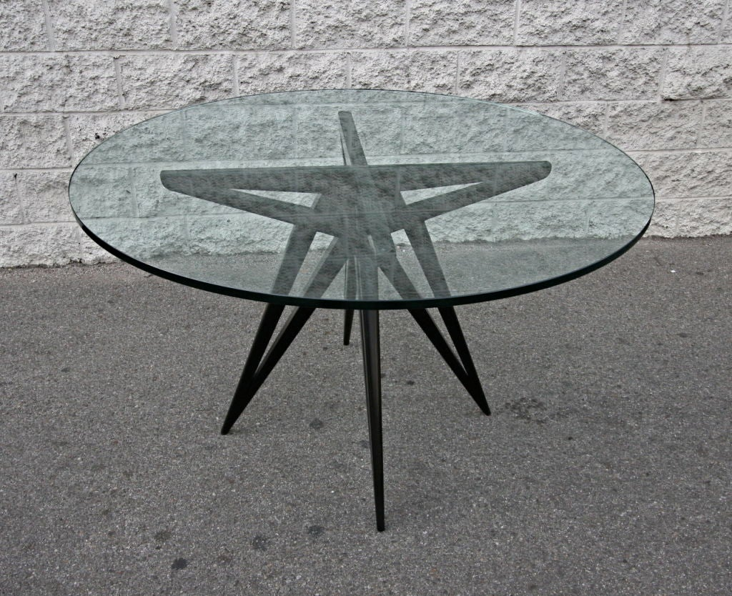 Custom star leg round ebonized wood dining table for four with a glass top by Adesso Imports  Can be done in different woods or with a wood top.