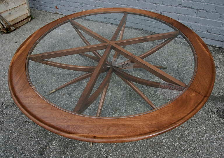 Custom spider leg round coffee table by Adesso Studio, made of walnut with brass feet and glass top.