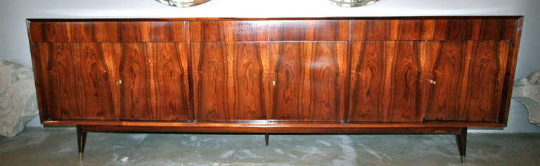 Long Brazilian jacaranda sideboard with three cabinets with shelves.