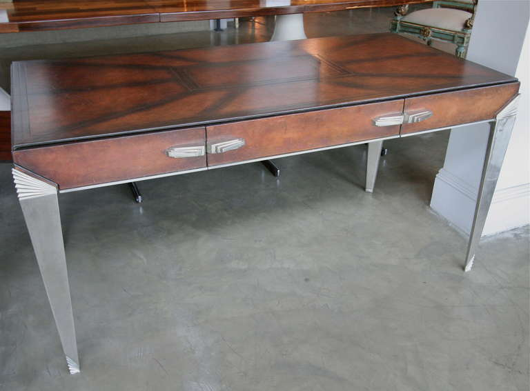 Gorgeous Art Deco console table from the 1930s that can also function as desk. Beautiful metal legs and drawer pulls, covered in leather.