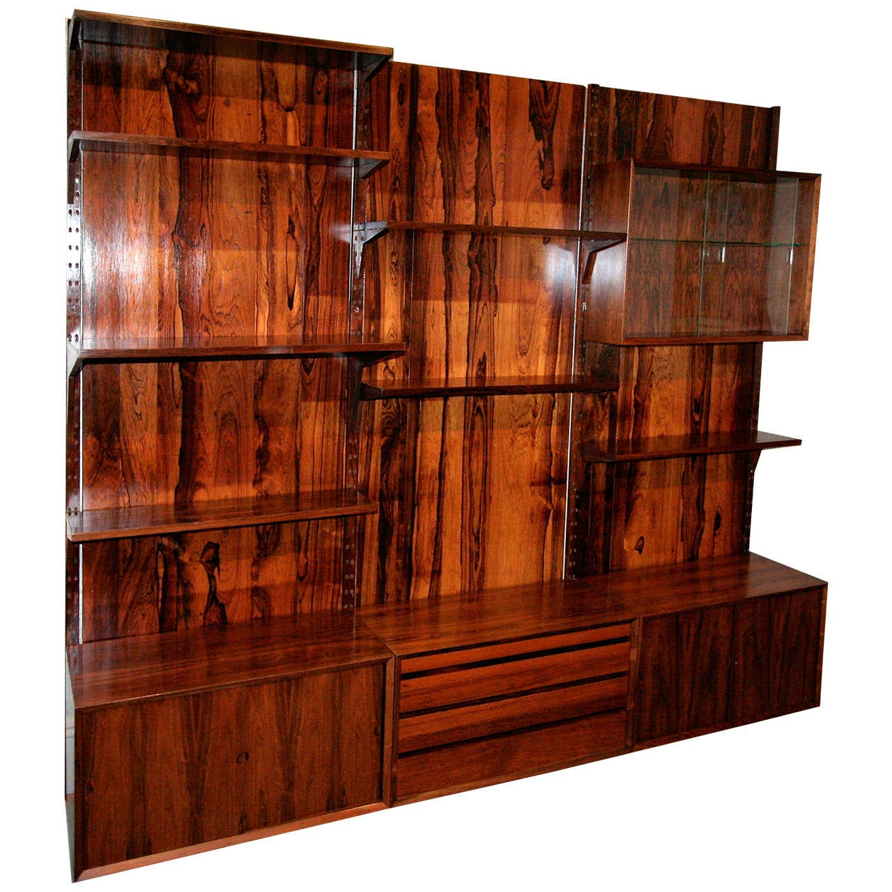 Brazilian jacaranda wood shelving unit from the 1960s with adjustable shelves and cabinets. Two hanging cabinets, one with glass doors, the other with jacaranda doors (not shown). Three cabinets at bottom, two with one shelf, the other with drawers.