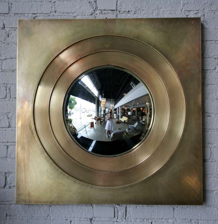 Custom convex mirror sunken into concentric circles of brass.