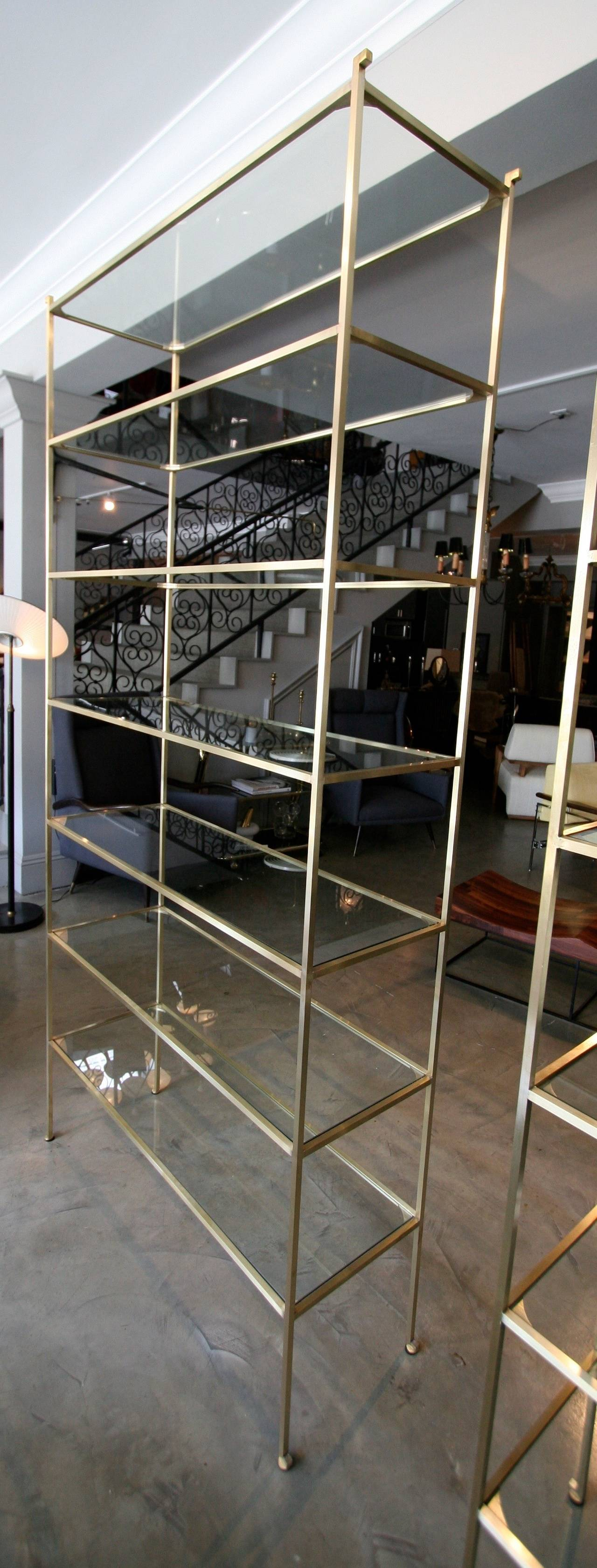 Pair of tall custom brass étagères with seven glass shelves. Can be made in custom size and finish.