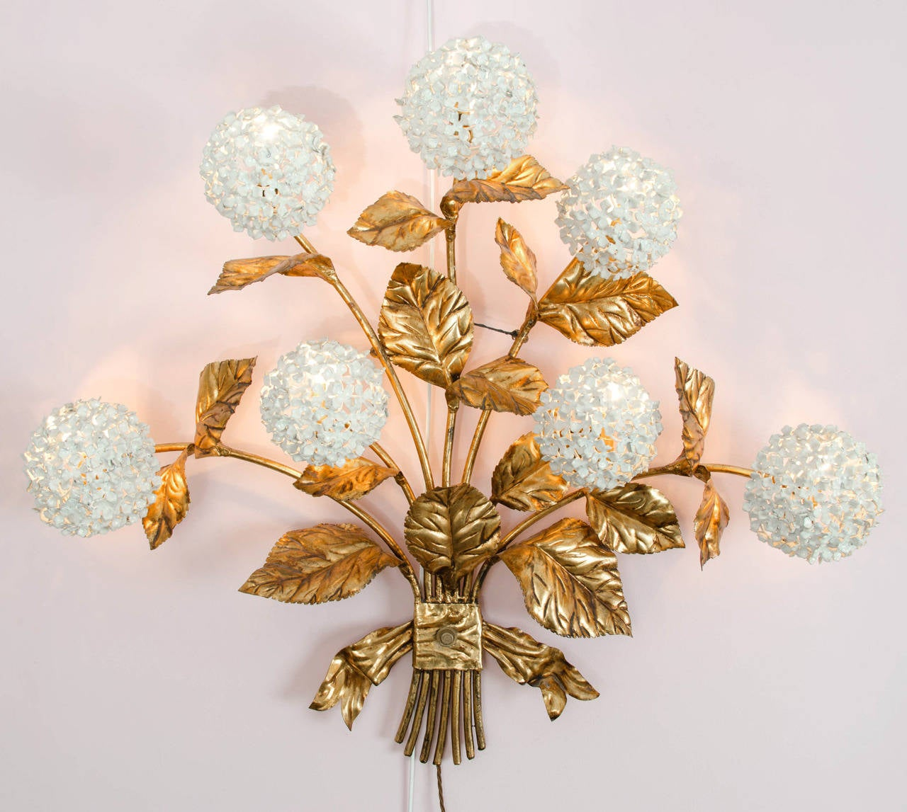 Rare American 1950s wall light in gilded brass with white enamel hydrangeas in the form of an ornate bouquet. An abundance of leaves with seven flowers in full bloom each giving a glamorous diffused light. Matching standard lamp and wall light