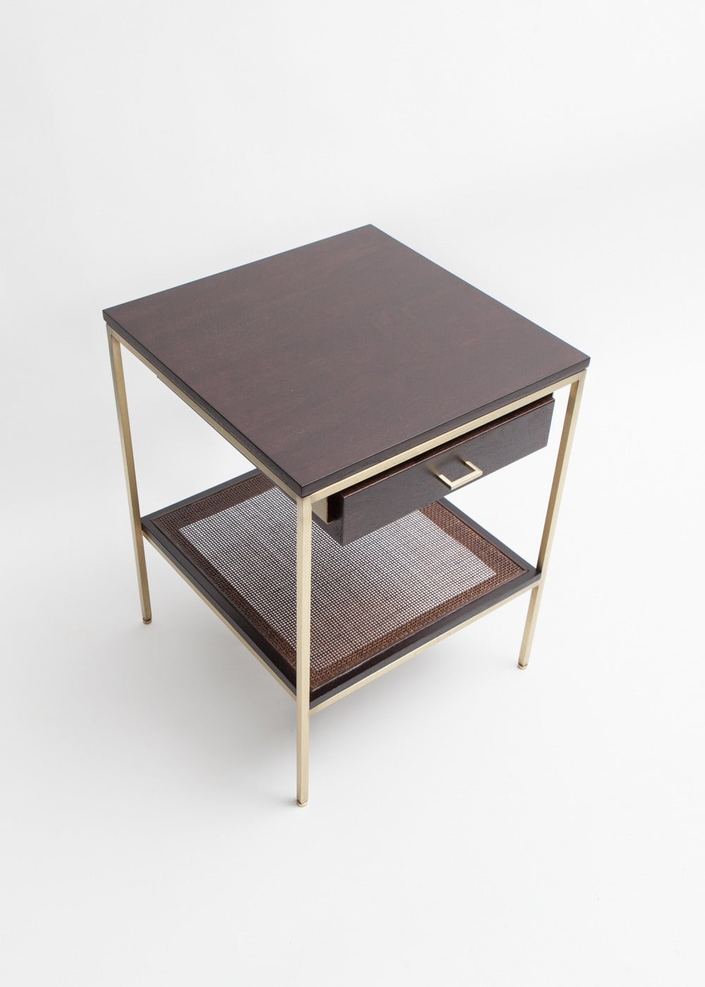 Pair of reGeneration custom bedside tables which are made to order. They are shown here with an ebonized wood top and drawer with cane shelf. The frame and hardware are brass-plated steel.