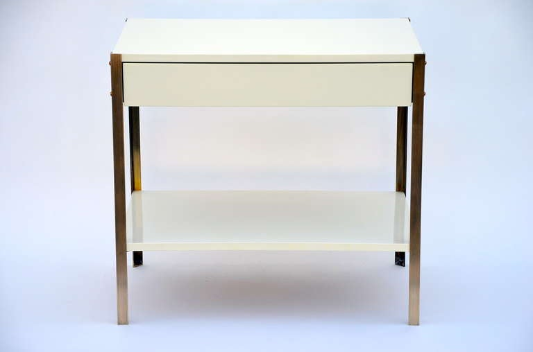 Pair of Minimalist ivory lacquer and brass nightstands.  Bottom shelf height: 6.5 in. tall.  Soft close drawer glides.  Also sold individually.