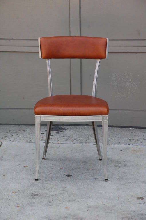 Set of 4 neoclassical aluminum and brown leather dining chairs. Very sturdy and confortable.