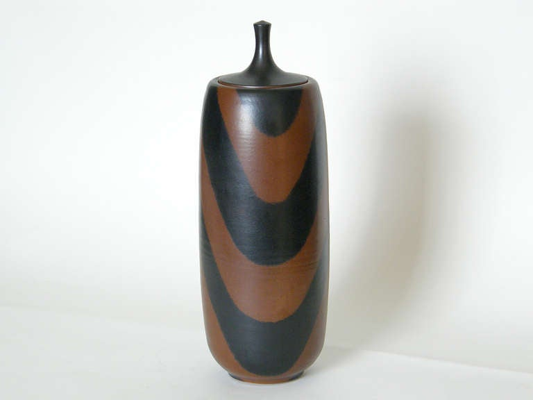 Lidded ceramic jar by California potter Harrison Mcintosh. The simple, elegant form is boldly decorated with thick, black, waving lines on a brown background. The refinement of the shape and glaze create a piece with tactile appeal typical of the