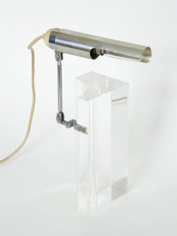 This acrylic block table lamp with articulated arm was designed by Filippo Panseca for Arteluce. It can be positioned in various ways. It's a nice example of high-design that's fun to play with.  Please contact us if you have any questions.