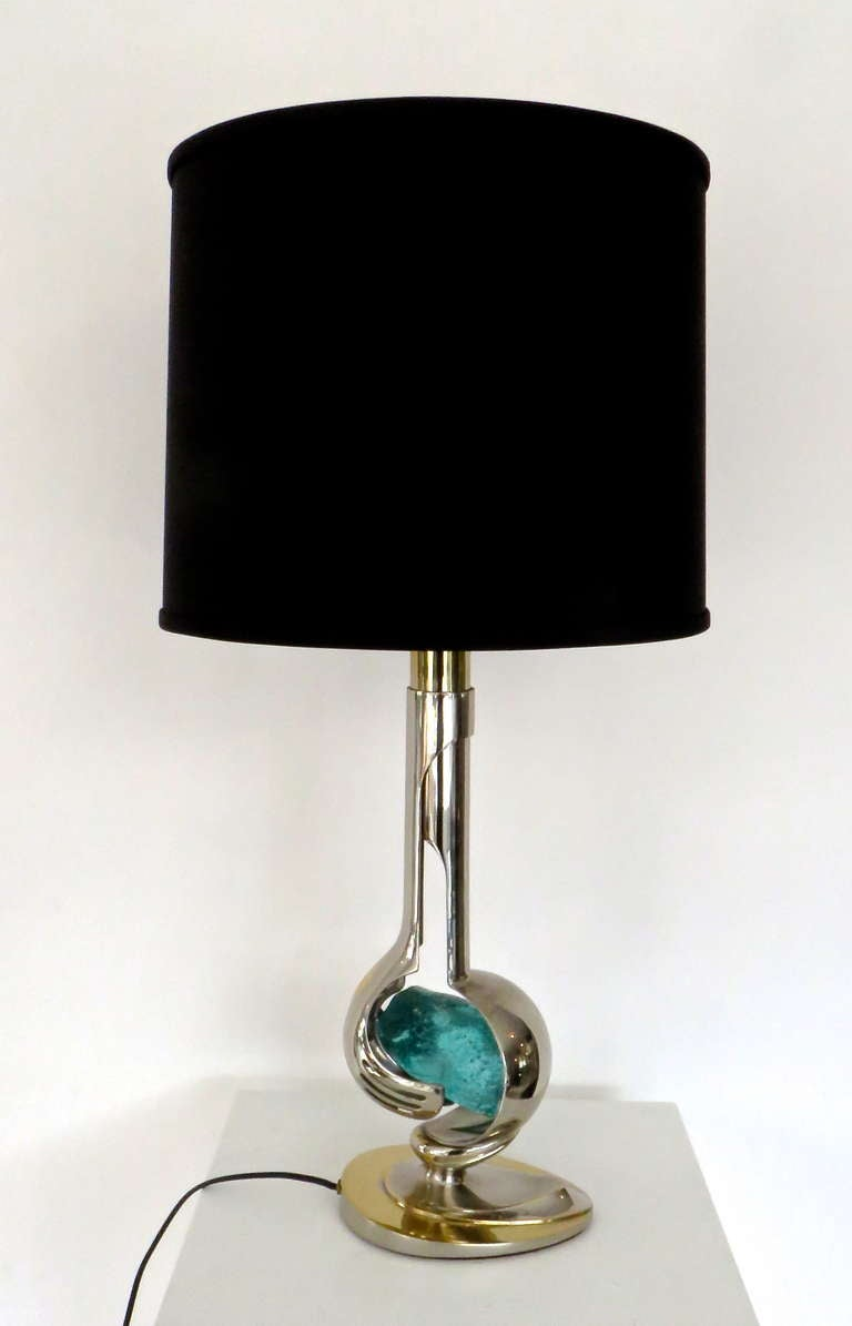 French table lamp two metals, nickel chrome and brass encasing a blue glass rock. By Willy Daro. Can accommodate a three way bulb. Dimmer switch on socket. Measures: Lamp: 6