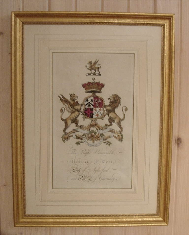 Pair of 18th century hand-colored armorial engravings in giltwood frames.