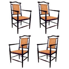 set of four anglo indian style ebonized wood and cane arm chairs