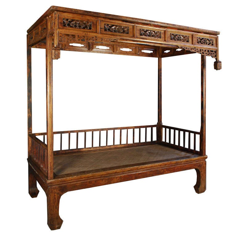 This is a wonderful example of a c.1800 canopy bed from Shandong Province, China. Made of Chinese Northern Elm, this bed features hoofed feet and multiple floral carvings.
