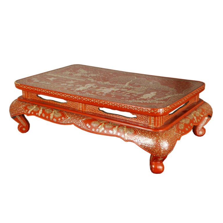 An early 20th century Chinese red lacquer and mother-of-pearl inlaid tea table depicting scholars at leisure in a courtyard landscape with garden pavilion, willow tree, flying geese, and billowing clouds.  