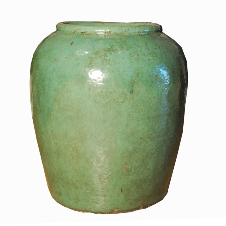 A 19th century Chinese celadon glazed ceramic urn with wide opening.