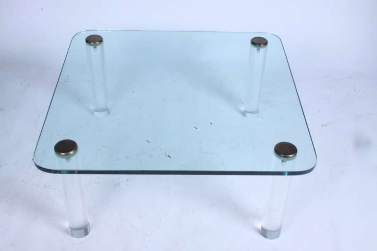 1970s, thick Lucite leg table with brass caps and rounded corner glass top. Lucite legs are 3