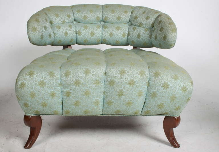 Pair of elegant tufted slipper chairs with curved backs and splayed legs.