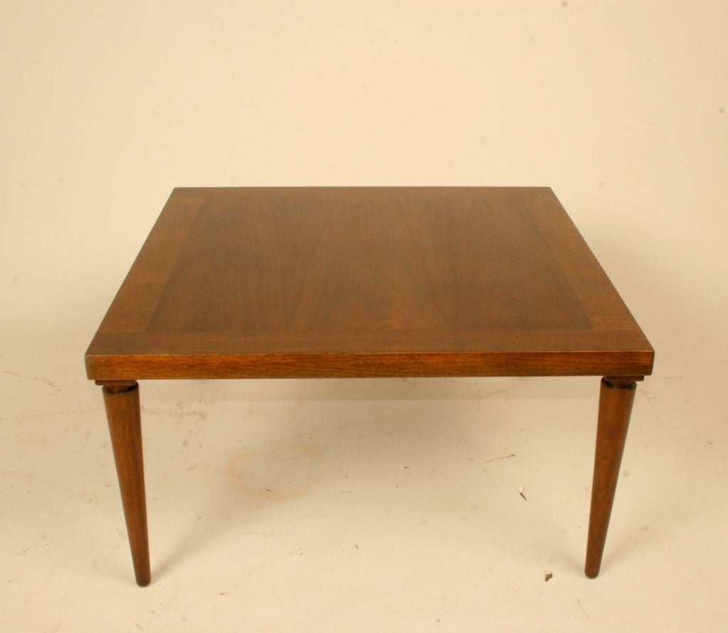 Walnut table designed by T. H. Robsjohn-Gibbings for Widicomb, rectangular table with tapered legs with notch in at top.