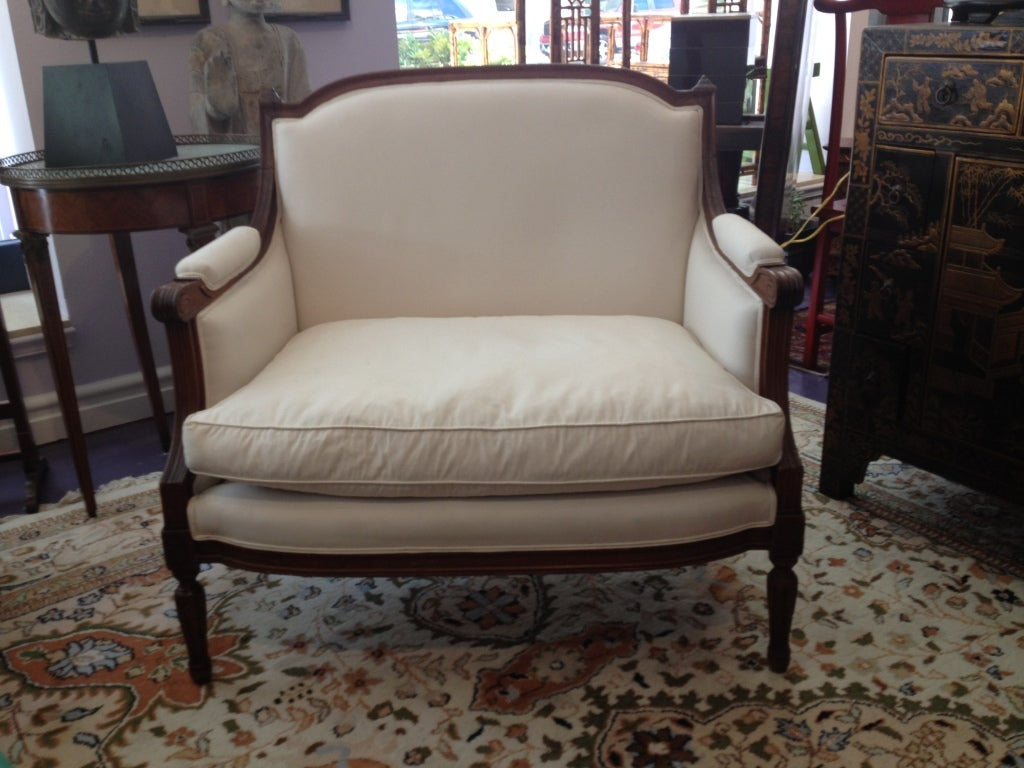 A French Louis XVI style fruitwood Marquise bergere/arm chair upholstered in white cotton with down filling, rare extra wide design with padded arms,  hand carved finials to the top corners.