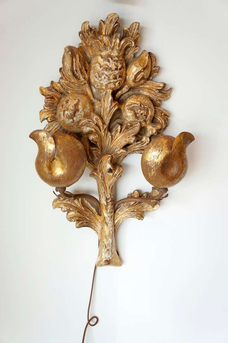 A pair of Italian intricately hand-carved and gilded wall lights. Newly wired with brown silk flat cord and a single pole switch. Orange peel formed diffusers back light the carved fruit forms.