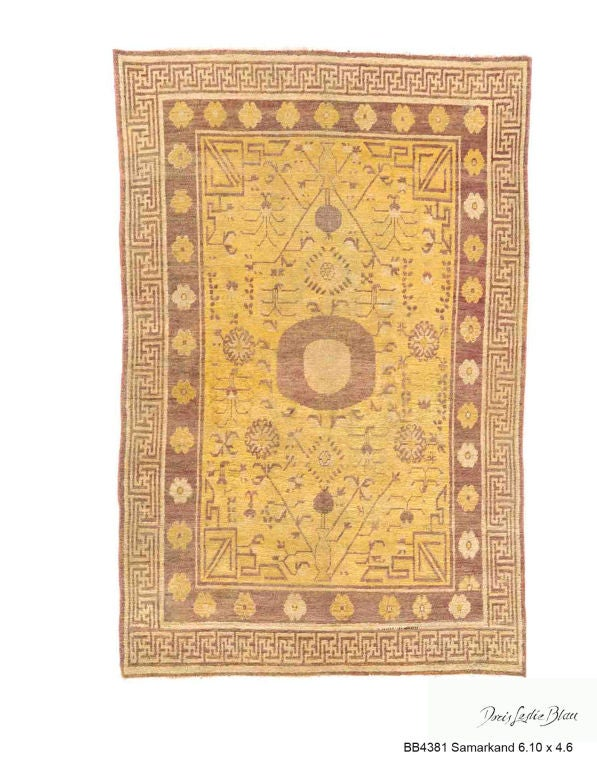An early 20th century Samarkand (Khotan) carpet, the yellow field with angular vines, flower heads and a pair of vases around a central light brown roundel with a solid beige centerpiece with a beige fretwork border.