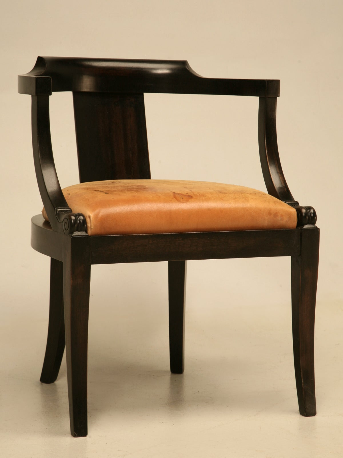Antique French solid mahogany desk chair in a beautiful ebonized finish that lets the warm brown tones of the wood to gently peek through the black. The seat cushion is old leather with new padding underneath and the frame has been properly