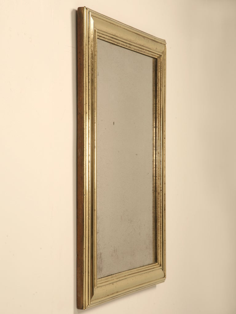 Outstanding original authentic antique French bistro mirror with its remarkable brass over wood frame and its original mirror that's just starting to sugar. The brass frame has just been polished with only minute bits of tarnish left showing